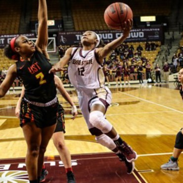 A Texas State basketball player heads off against a University of St. Thomas player.