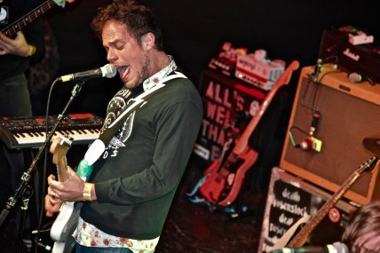 Jeff Rosenstock, red faced, plays his guitar and loudly sings into his microphone.