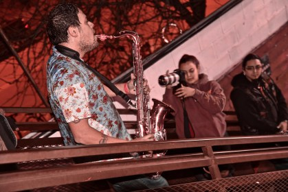 A side view of Rosenstock playing his saxophone on the balcony.