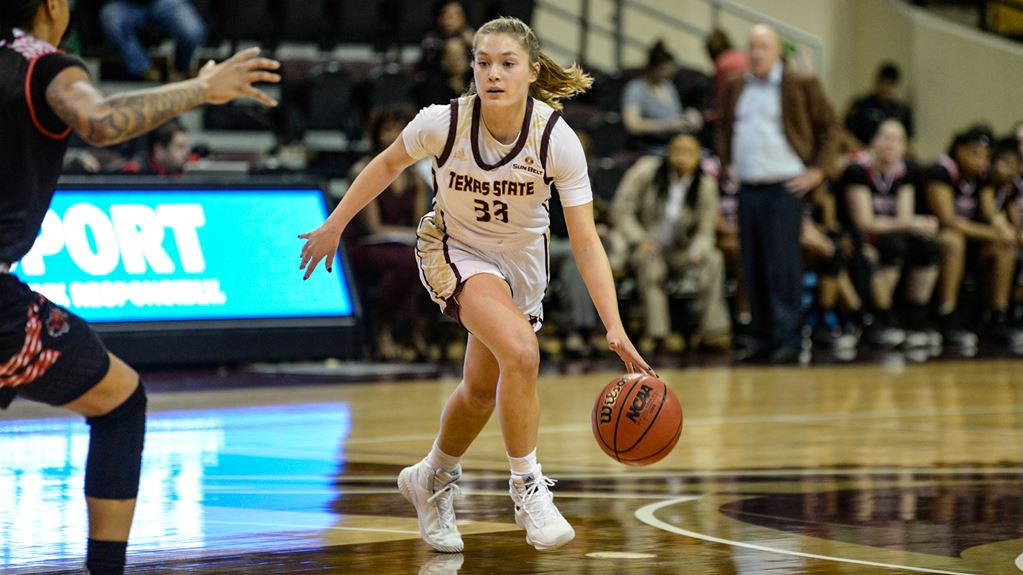 A girl with a blonde ponytail dribbles the basketball defensively.