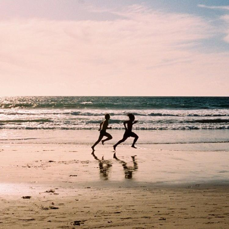 Two people running down the beach