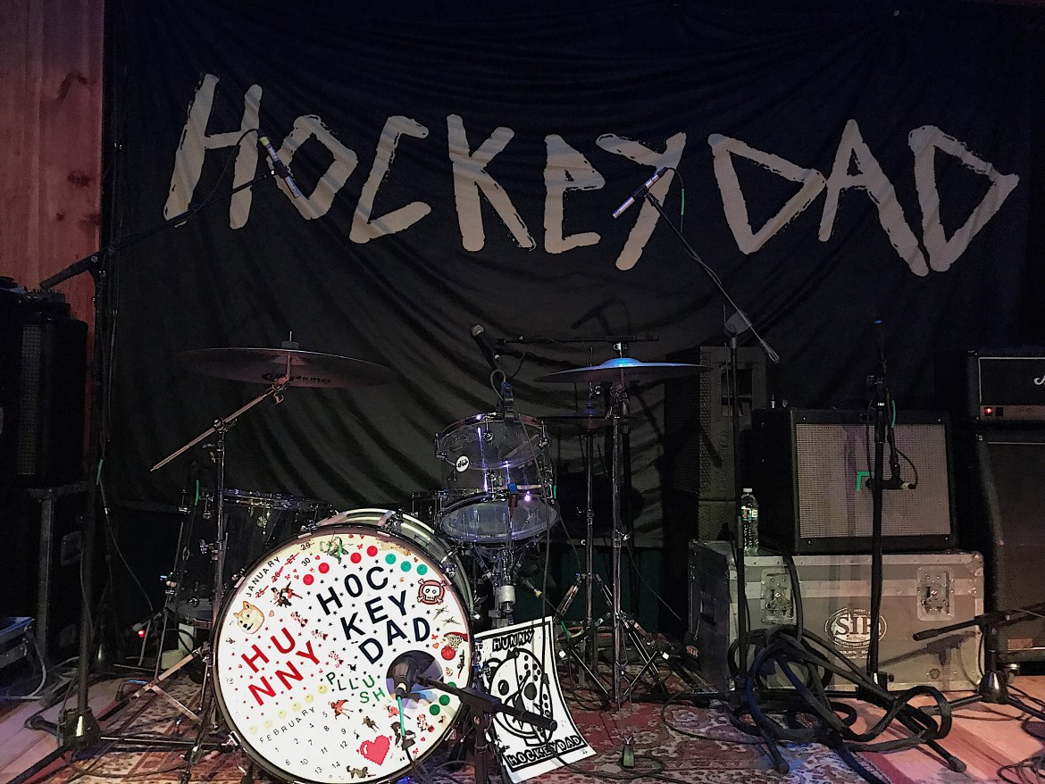 """A banner with """"Hockey Dad"""" on it and a drum kit decorated with stickers spelling the band names."""