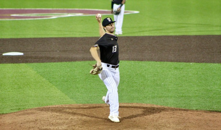 A pitcher in baseball getting ready to throw the ball to the batter of the opposing team.