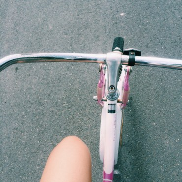 The image features a top view of a bike's metal handlebars.