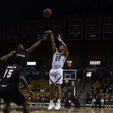 Nijal Pearson shoots over a Louisiana player for three as guards Jaylen Shead and Tre Nottingham look on.