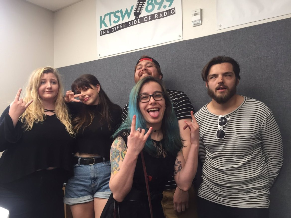 2 guys and 3 girls pose in front of KTSW banner.