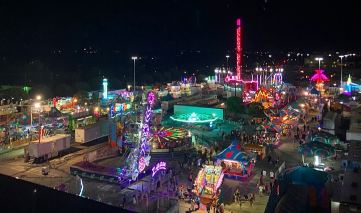 The view of a carnival at night from the top of the ferris wheel.
