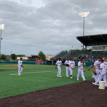The Texas State baseball team share smiles and high fives in warmups before their matchup with the Houston Baptist Huskies on April 16, 2019.