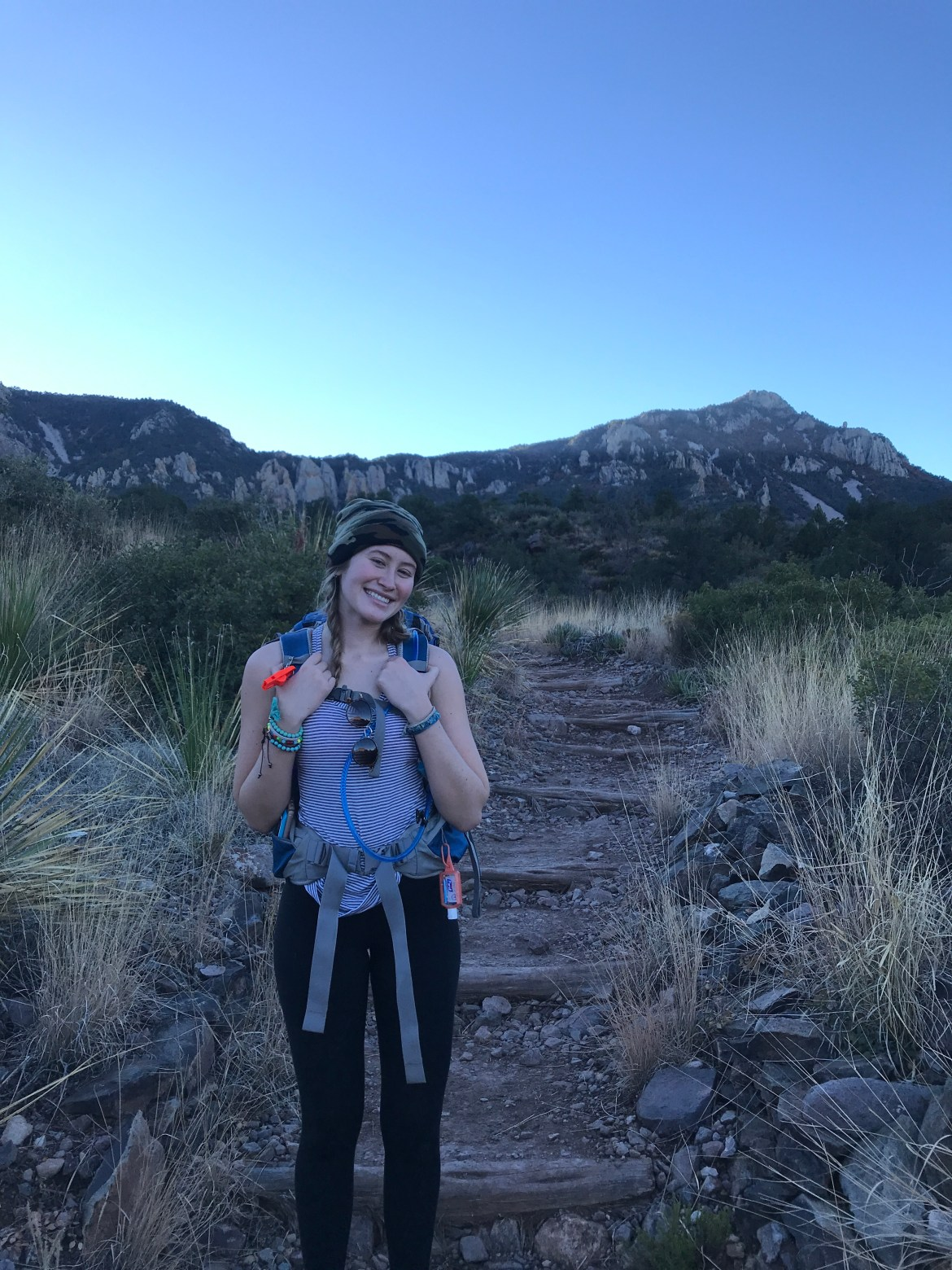 White blonde girl standing at the start of a trail with mountains in background