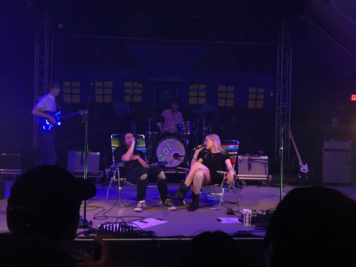 Phoebe Bridgers and Conor Oberst sit in lawn chairs singing.