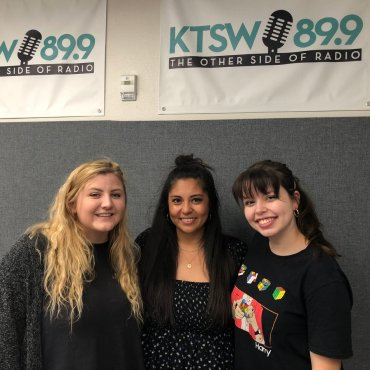 3 pretty ladies stand in front of a KTSW banner.