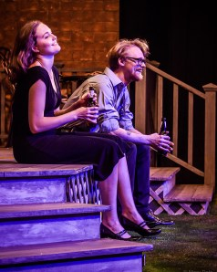 A girl and man sitting on a porch laughing
