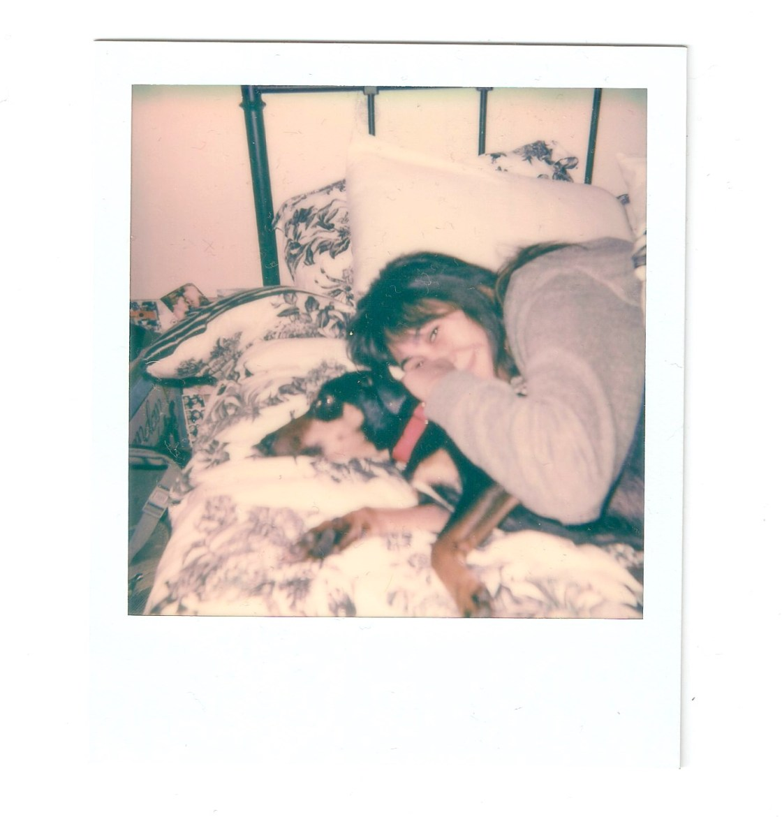 The white framed polaroid photo features a girl laying on a bed with a dog
