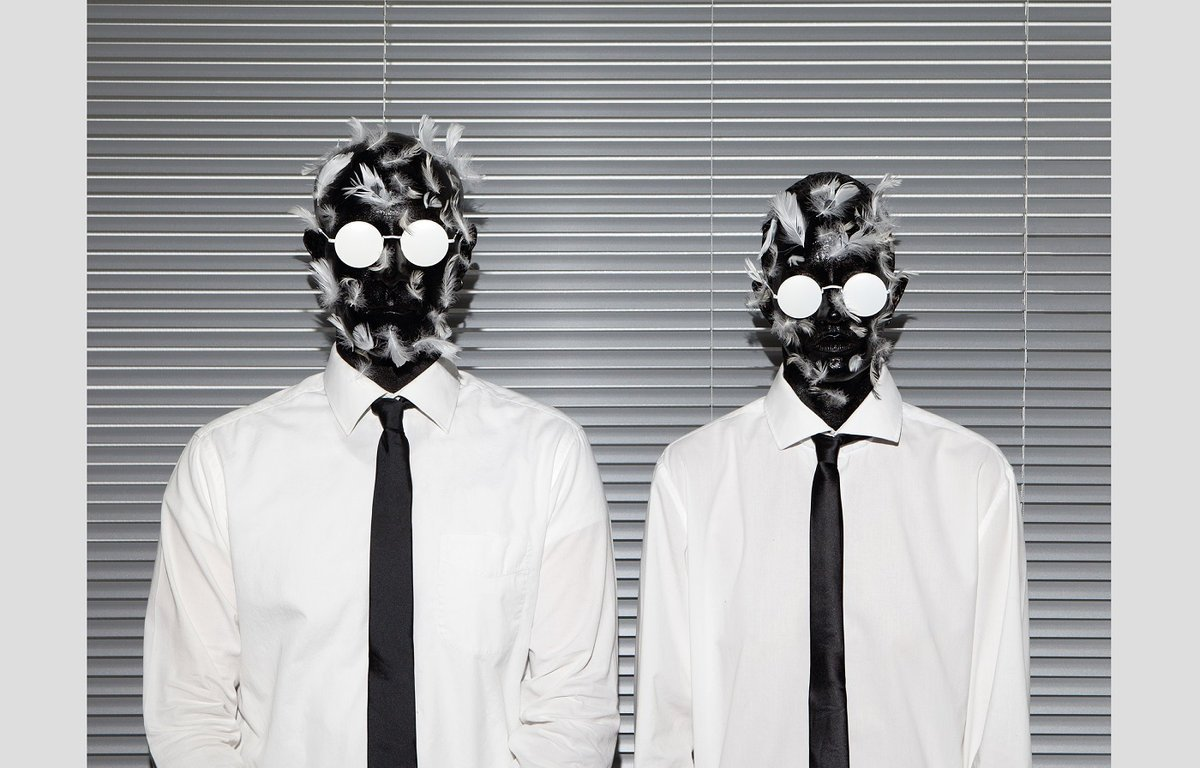 Two people each wearing a shirt and tie, with stark white glasses and their heads covered with tar and feathers, standing next to each other in front of a closed window shade.