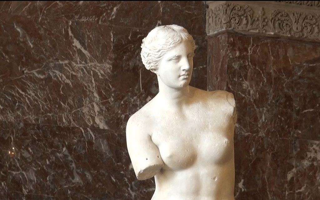 A picture of an armless Greek statue in front of foliage.