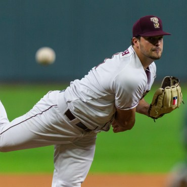 Finishing his throwing motion, Reich watches his pitch head toward the plate in a maroon hat, white jersey, and white pants.