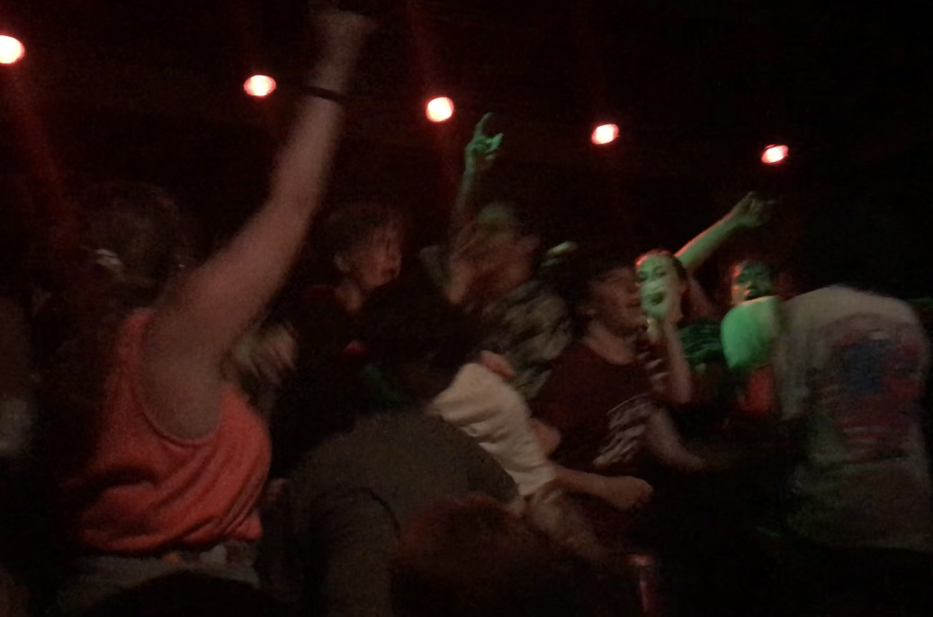 Multiple people on stage dancing and waving their arms in the air.