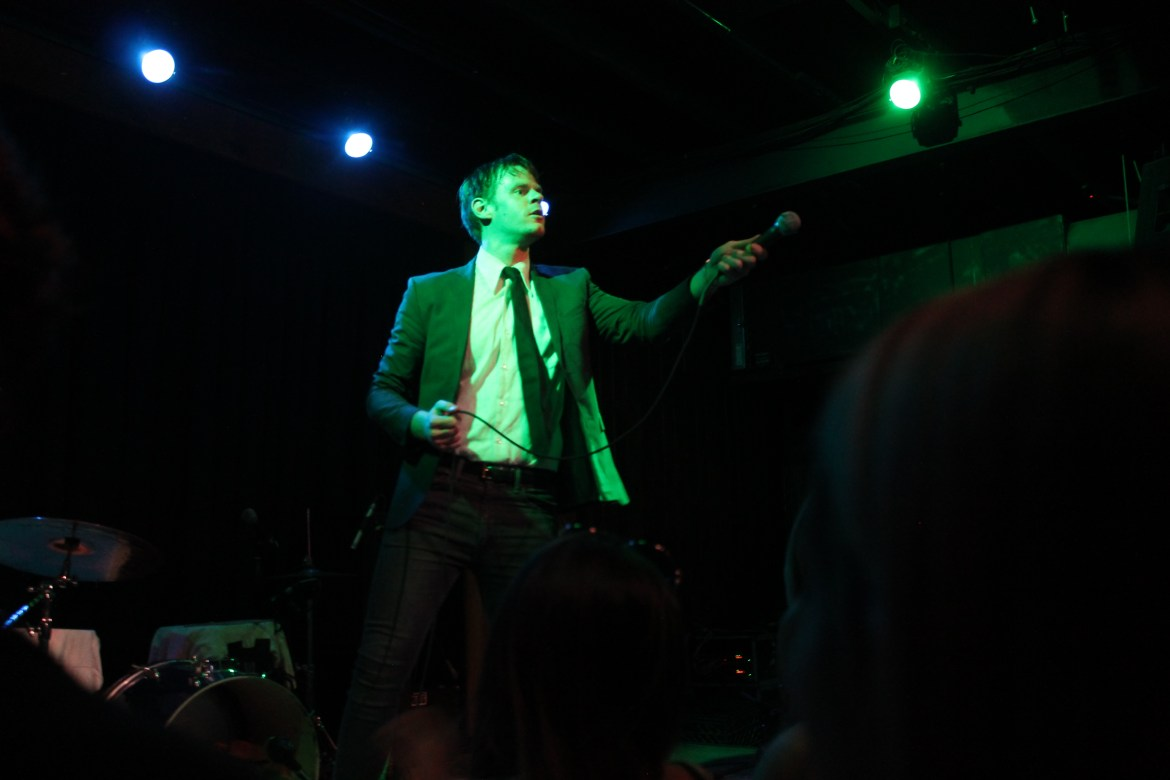 One man with blonde hair and a suit on reaching his microphone out into the audience.