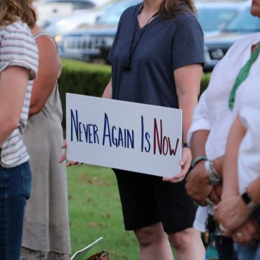 """A lady in a blue shirt holds a sign saying """"never again is now."""""""