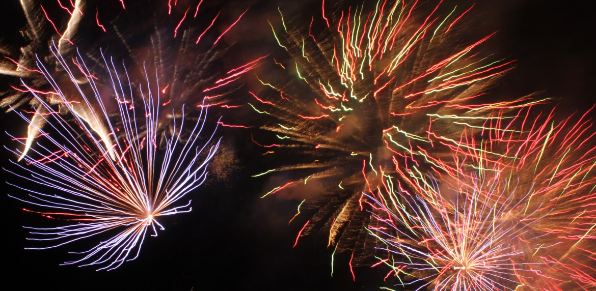Three fireworks of all different colors bursting in the dark sky.