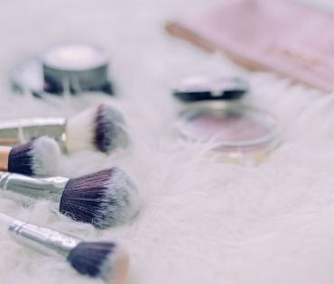 Makeup brushes and two cosmetic products on top of white fur