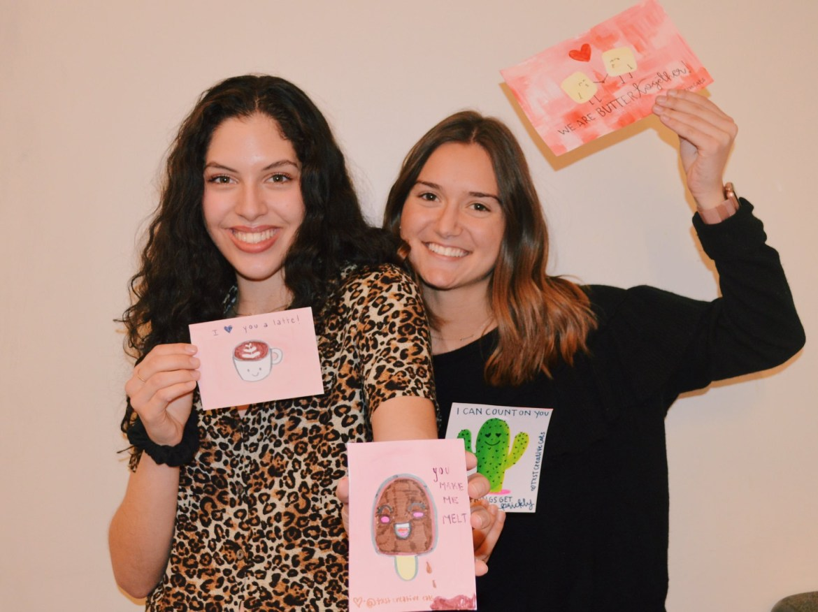 Two Creative Cats members holding up their Valentine's Day cards