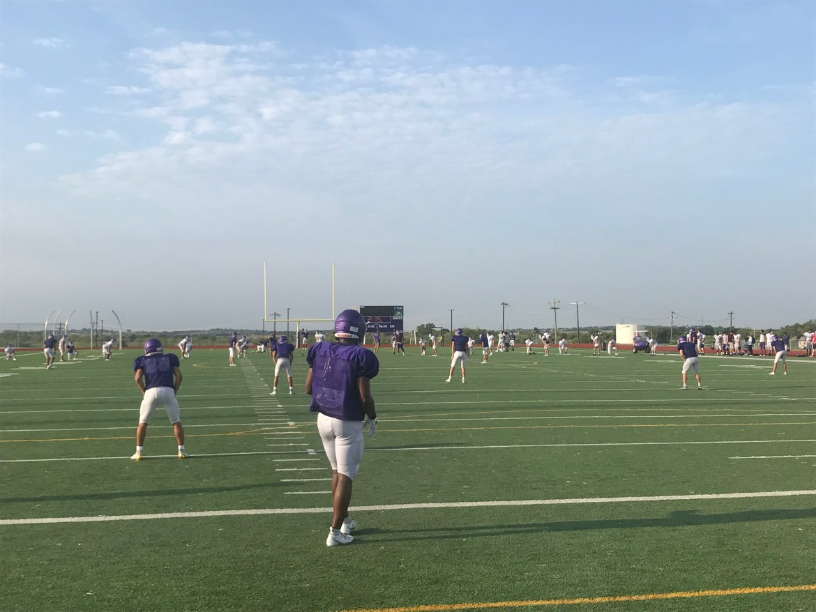 San Marcos players wearing pads, helmets, and purple jerseys prepare to return a kickoff.