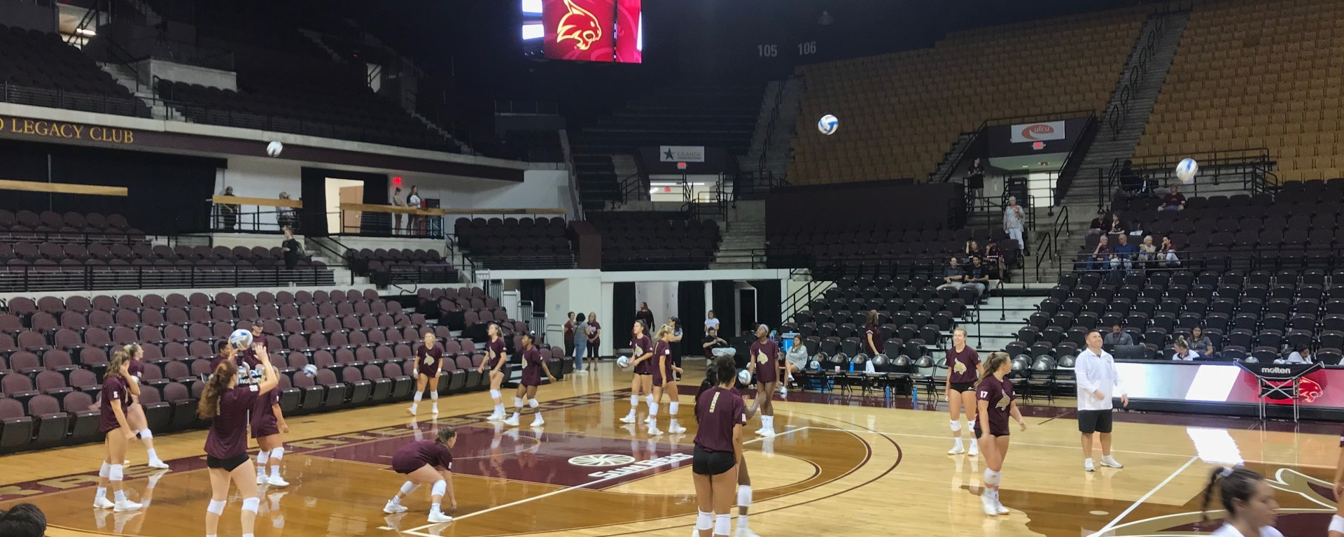 5 or so Bobcats are are standing on opposite sides of their side of the court warming up with volleyballs before the game starts.