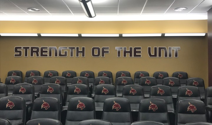 """""""Strength of the Unit"""" is in bold maroon letters at the top of Texas State's press conference room."""