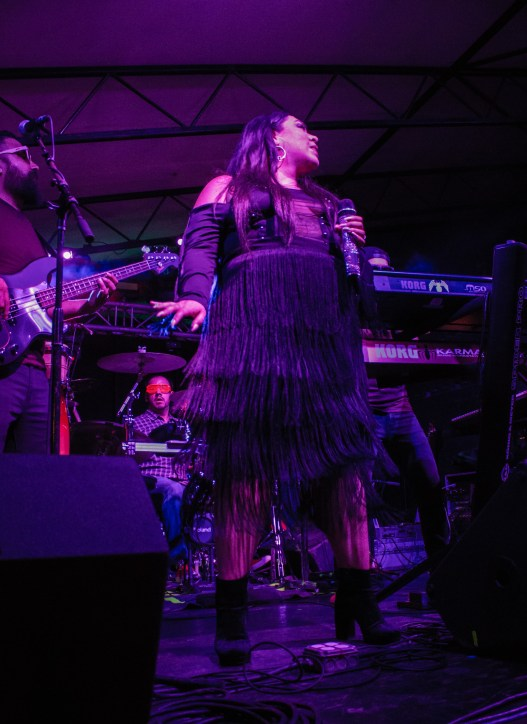 The vertical photo features a woman standing on a stage in an all-fringe black outfit.