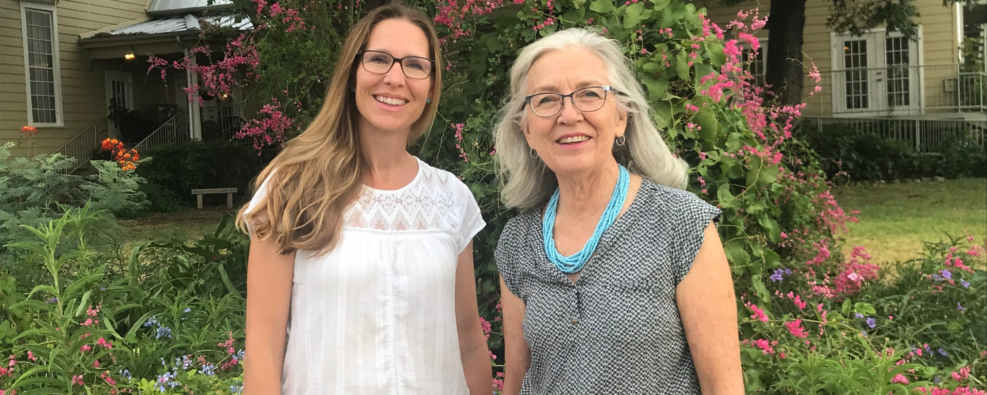 New Executive director Virginia Condie (left) and Former Executive Director Dianne Wassenich (right) stand in front of bush with ample pink flowers.