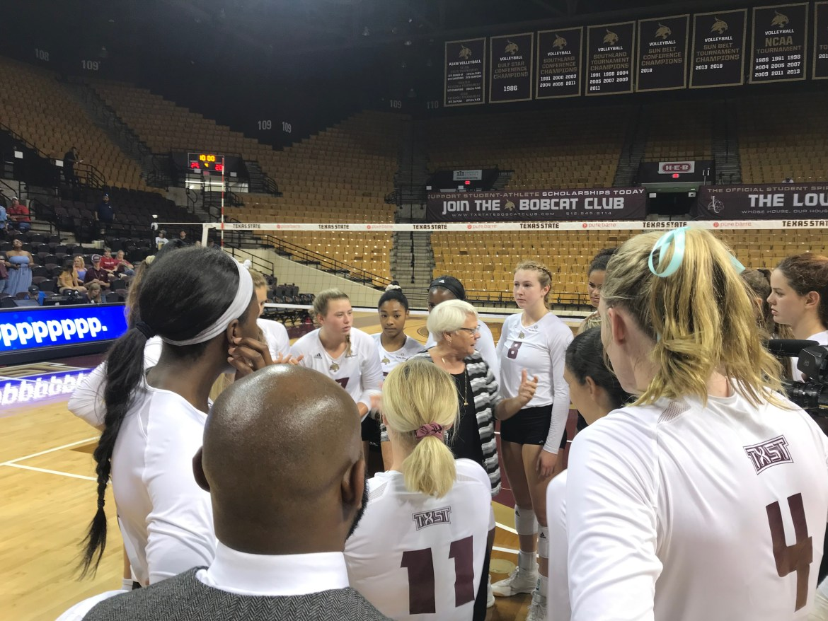 Head coach Karen Chisum stands in the middle of the circle of Bobcats on the home court side talking to her team about the game.