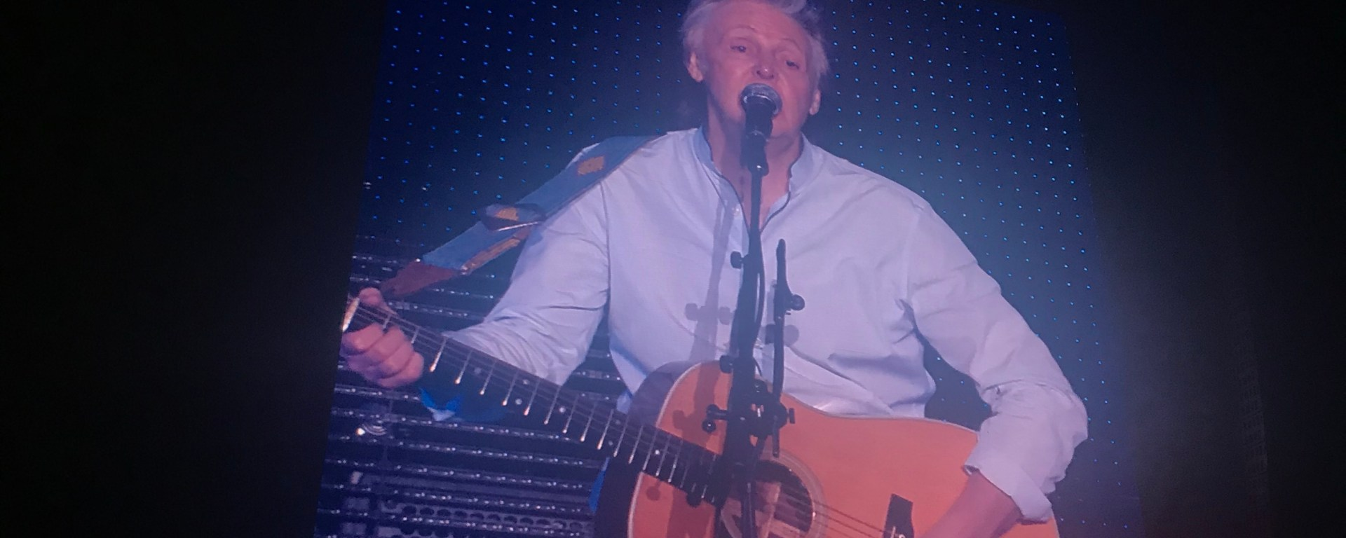 A photo from a concert showing Paul McCartney on stage looking and singing at the crowd while playing his acoustic guitar.
