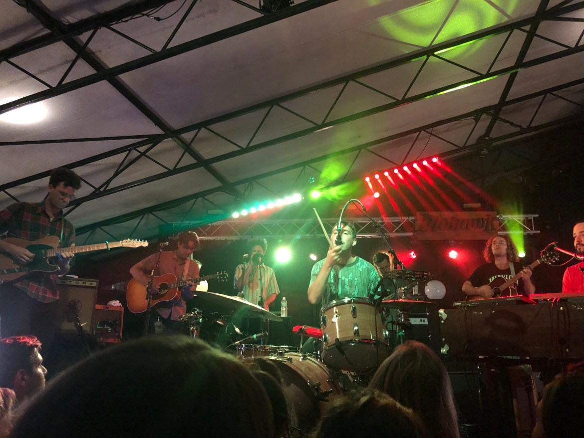 The picture shows all members playing their instruments (3 guitarists, one bassist, and two keyboardists) while the drummer sings into a microphone with a single drumstick in his left hand.