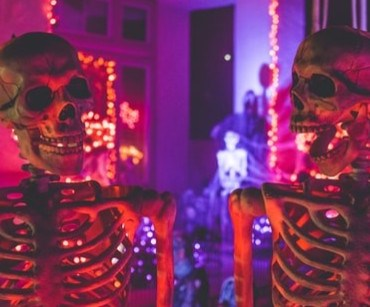 Two skeletons surrounded by orange and purple lights