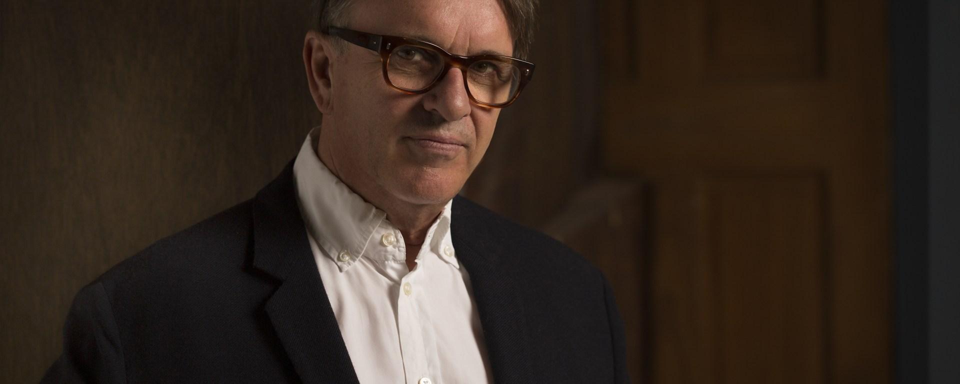 Photograph of a slightly older gentleman with dark-framed glasses