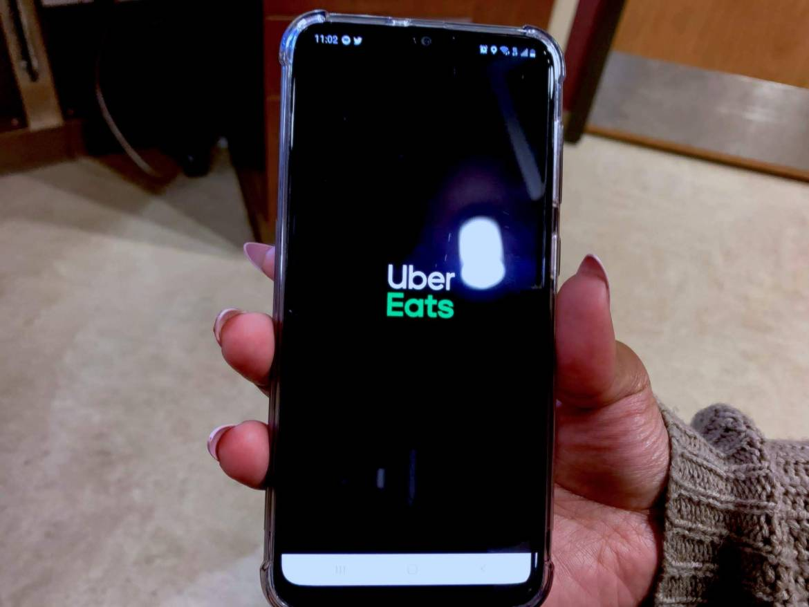 UberEats App cover page on a phone, a black background with Uber in white and Eats in green.