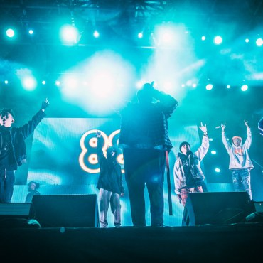The Group, 88rising, performing on stage at their 88 Degrees and Rising Tour, The Higher Brothers, Rich Brian, and August 08 are seen on stage with an 88 logo in the background.