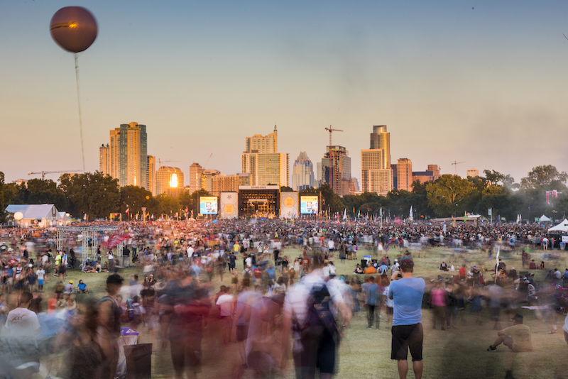 View of the main stage at Austin City Limits Music Festival with the Austin skyline and people buzzing by at sunset.