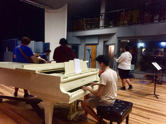 In the foreground, a student plays a white piano, facing away from the camera. Behind the piano, three students stand facing away from the camera. Dr. Jose Garza can be seen playing the bass in the background. The focus in this picture is on the architecture of the room to show its usefulness for recording.