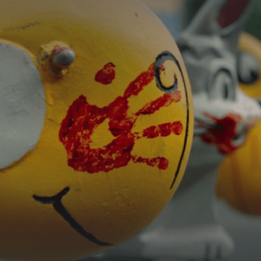 A yellow fish spring rider playground toy covered in a bloody handprint