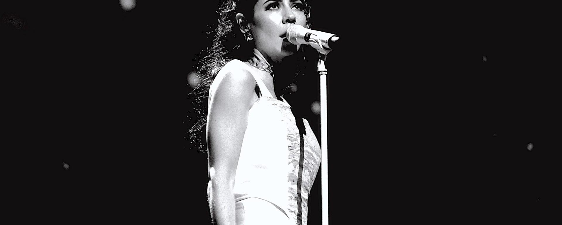 Black and white photo of Marina Diamandis singing on a stage.