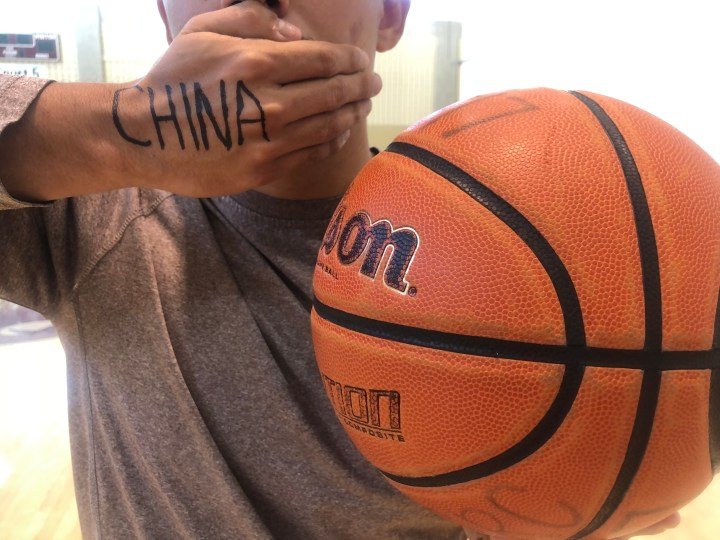 """A man stands with his hand over his mouth and """"China"""" written on it, with a basketball in the other hand"""
