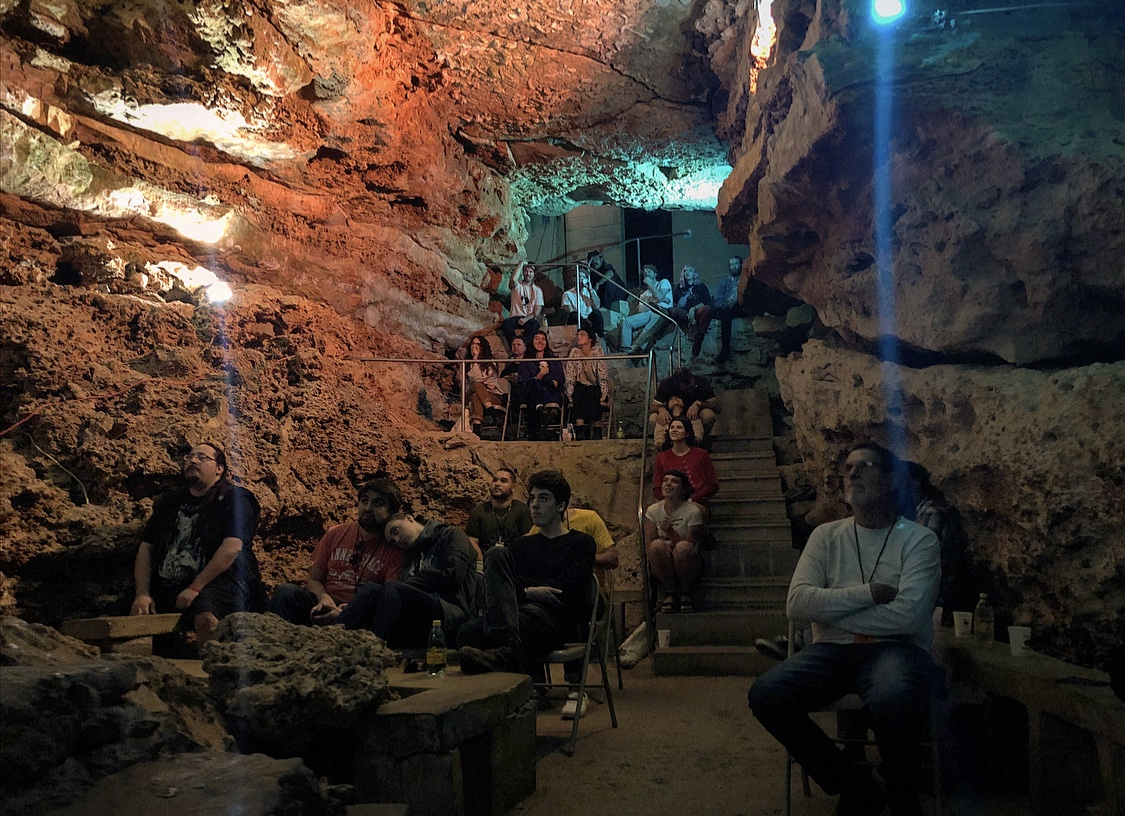 An audience watching a movie screening inside a cave.