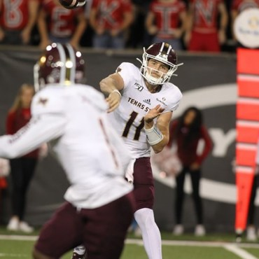 Bobcat quarterback in maroon pants and helmet and white passes the ball to a receiver.