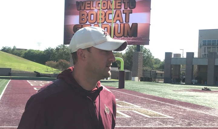 """Jake Spavital stands on the corner of the football field talking to the media. In the background the billboard at Jim Wacker Field reads, """"Welcome to Bobcat Stadium."""""""