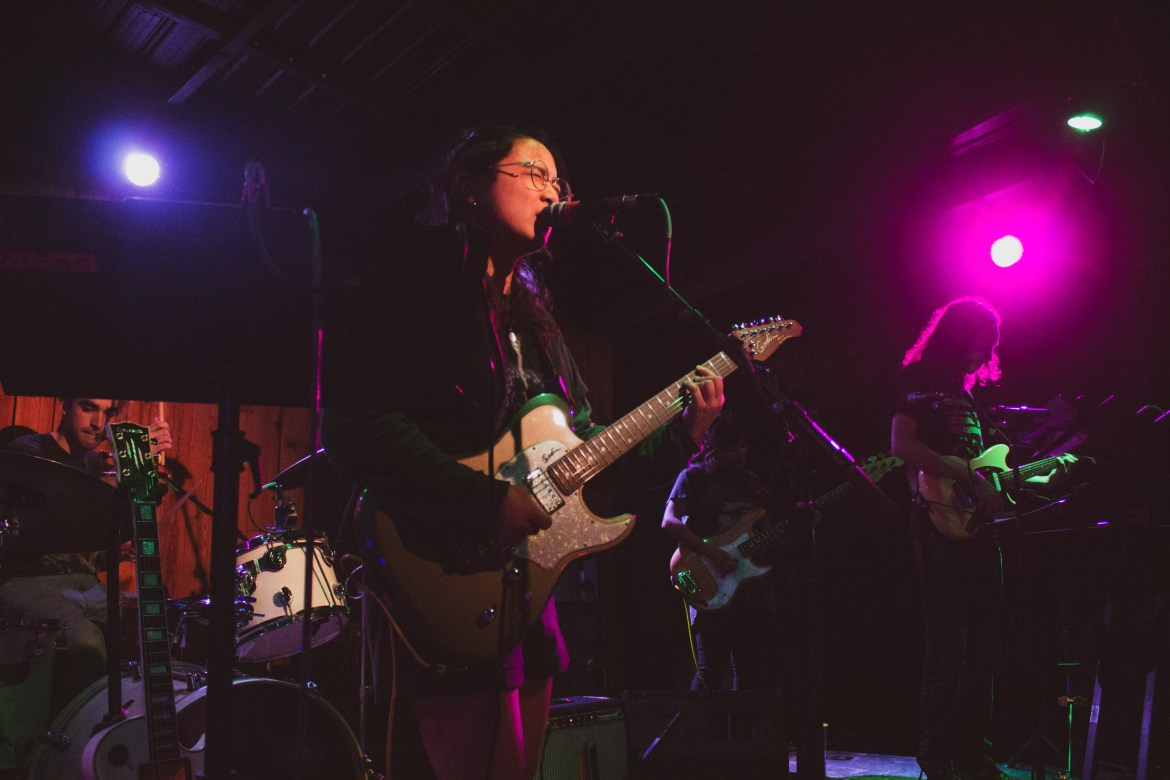 A young female in her early to mid-twenties with short, curly black hair wearing glasses singing and playing guitar in a band in a dark, neon-lit venue.