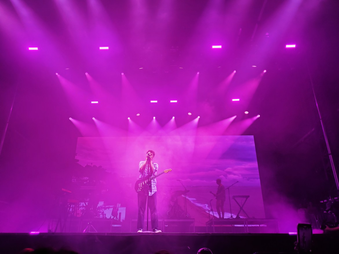 LANY performing at Austin City Limits. Paul Klein is in the center at the microphone. The background is a beach with a cloudy sky and the spotlights make the stage pink.