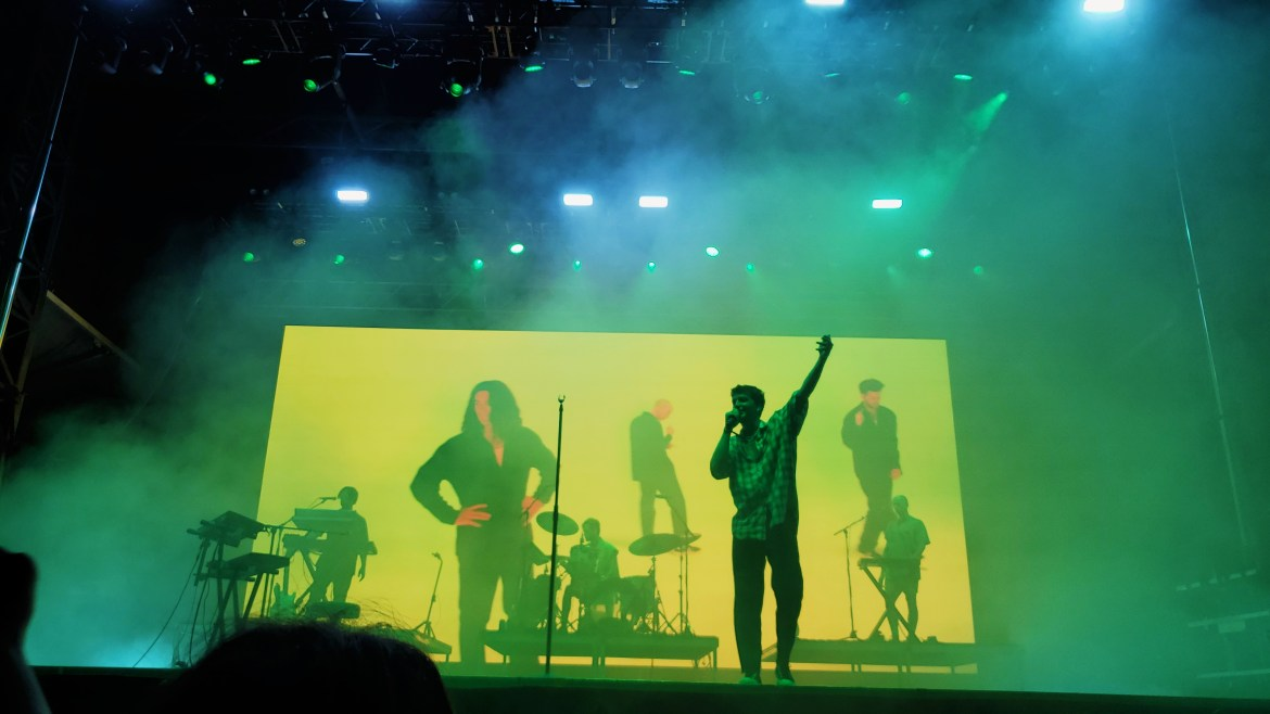 LANY performing at Austin City Limits. Paul Klein is in the foreground, singing with one hand raised. The guitarists and drummer are in the background. The backdrop is a video of the band from several years ago.