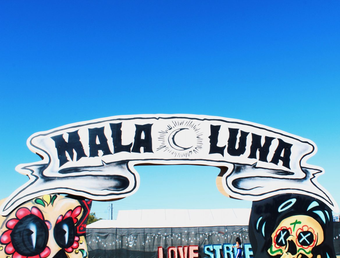 """A white sign made to look like a ribbon that says """"Mala Luna"""" in black capital letters. Between the words """"mala"""" and """"luna"""" there is a crescent moon with lines around it, made to look like a sun. Below and on each side of the sign there are colorful skulls painted like sugar skulls from Day of the Dead celebrations. The background is a blue sky."""
